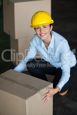 Portrait of female factory worker picking up cardboard boxes
