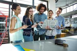 Smiling business team discussing over laptop in meeting
