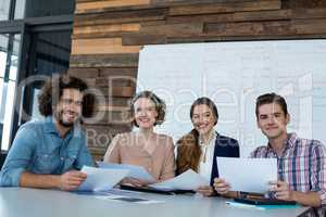 Smiling business executives sitting in office with document