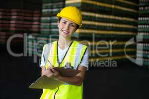 Smiling female factory worker writing on clipboard in factory