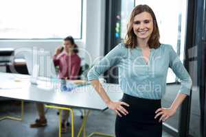 Business executive standing with hands on hip in office