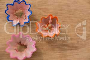 Colored pencil shavings in a flower shape on wooden background