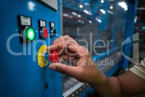 Hands of factory worker turning the control knob on the board