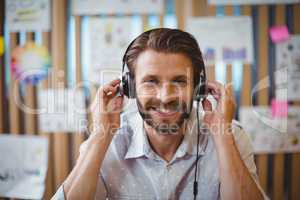 Close-up of male graphic designer listening music on headphone