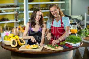 Two shop assistant chopping vegetables and fruits at counter