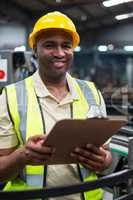 Smiling factory worker holding clipboard in factory
