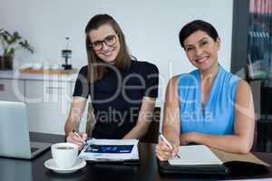 Portrait of smiling business executives discussing over clipboard at meeting