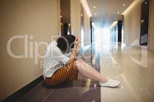 Sad female business executive sitting in corridor