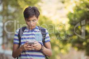 Schoolboy using mobile phone in campus
