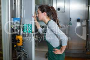 Female factory worker inspecting machinery