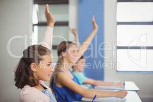Student raising hand in classroom