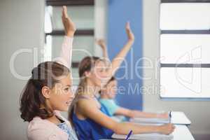 Student raising hand in classroom