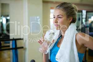 Thoughtful woman drinking water after workout