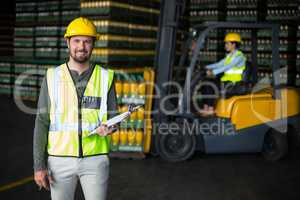 Portrait of factory worker holding clipboard