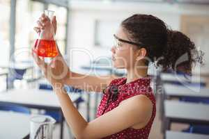 Attentive schoolgirl doing a chemical experiment in laboratory