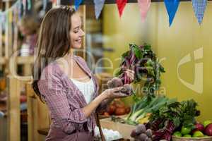 Woman choosing vegetables in grocery store