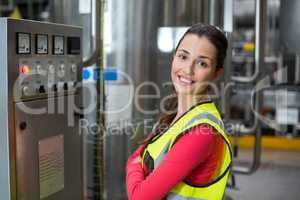 Portrait of female factory worker standing near machine