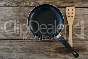 Pan and wooden spatula against wooden background