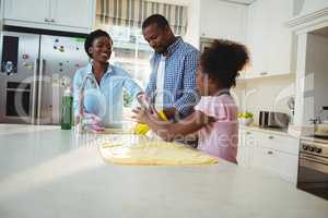 Family washing utensils in kitchen sink