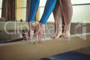 Female gymnast practicing gymnastics on the balance beam