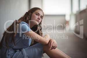 Thoughtful schoolgirl sitting in corridor