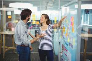 Male and female business executives discussing over whiteboard