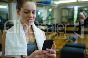 Beautiful fit woman using mobile phone after workout