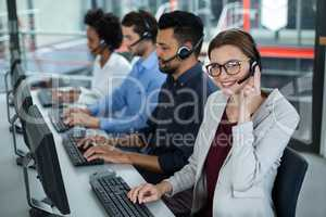 Business executives with headsets using computers at desk in office