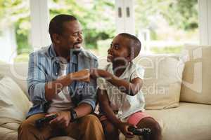 Father and son fist bumping while playing video game