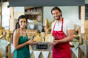 Portrait of smiling male staff and woman holding a basket of baguettes at counter