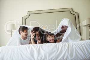 Happy family lying under blanket on bed at home