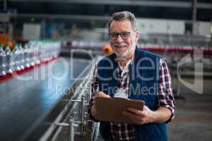 Portrait of smiling factory worker standing with a clipboard