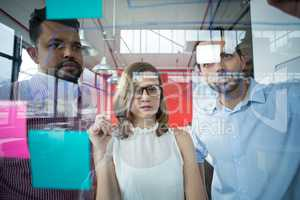 Business executives looking over sticky notes on glass