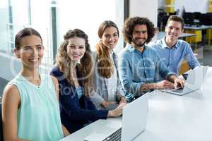 Portrait of smiling business team discussing over laptop in meeting