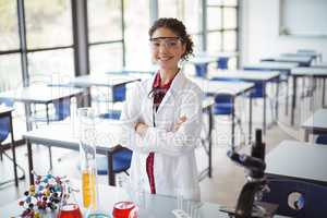 Portrait of schoolgirl in lab coat standing with arms crossed in laboratory