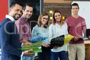 Smiling businesspeople standing with file and clipboard in office
