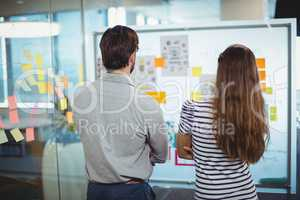Male and female business executives looking at whiteboard in office