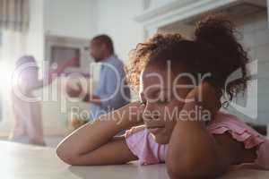 Sad girl fed up of her parents arguing in kitchen