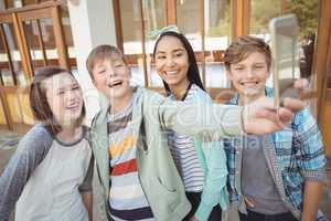 Group of school friends taking selfie with mobile phone