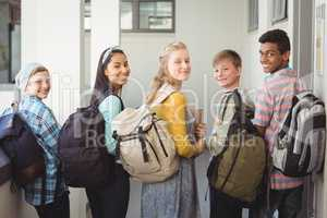 Portrait of smiling students standing with notebook and school bag in corridor