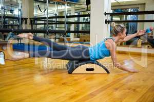 Determined woman exercising on arc barrel
