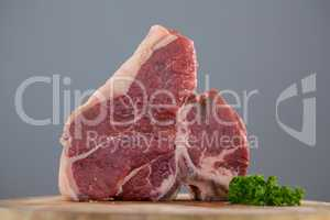 Sirloin chop and corainder leaves on wooden tray