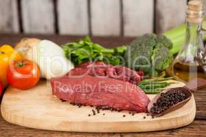 Beef steak on wooden board with ingredients
