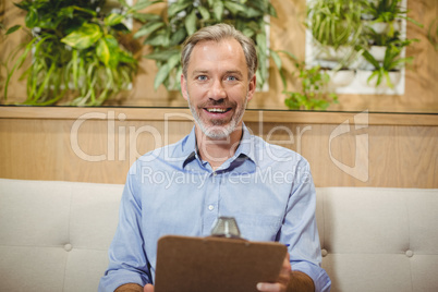 Smiling doctor holding clipboard in clinic