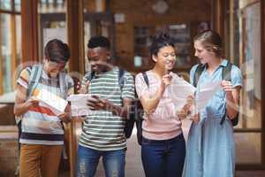 Happy classmates looking at grade cards in corridor