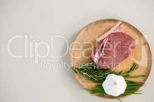 Sirloin chop, rosemary herb and garlic on wooden tray