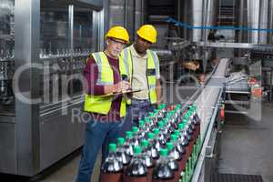 Two factory workers monitoring cold drink bottles in the plant