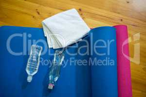 Exercise mat, towel and water bottles kept on wooden floor