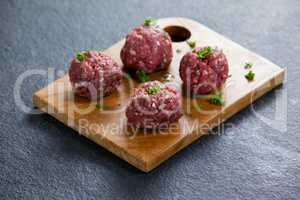 Minced beef garnished with coriander leaves on wooden board