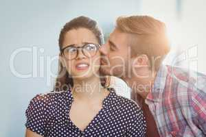 Affectionate man kissing woman